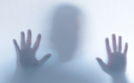 Defocused scary ghost silhouette behind a white glass background
